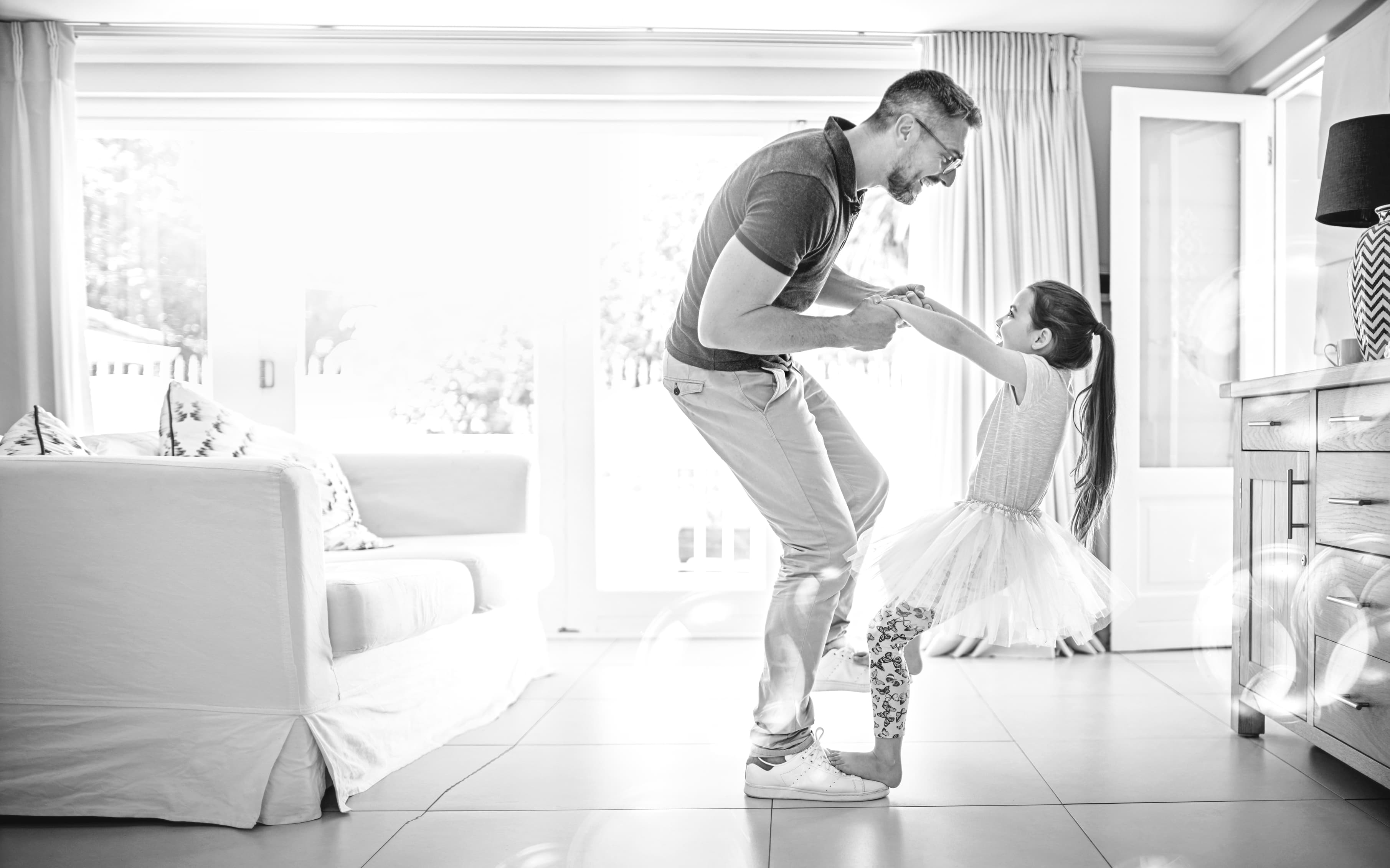 Father dancing with young daughter.