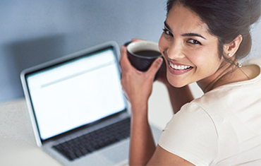 Happy woman drinking coffee at laptop.